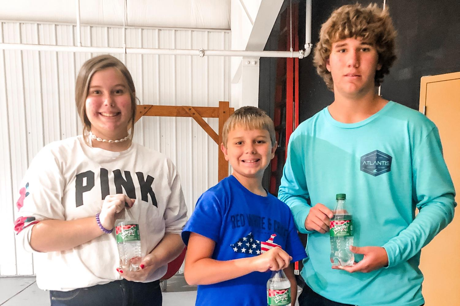 Bria, Gage, and Jhett proudly posing with their coveted Sprite Cranberry bottles.