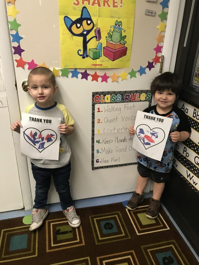 Two of our preschool students show off their artwork in honor of our Veterans.