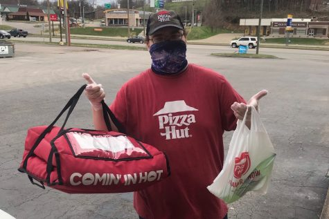 Pizza Hut employee Billy prepares to deliver an order, following all of the current safety guidelines.