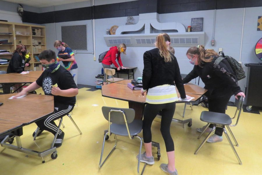 Sanitizing their area before moving to a different class has become part of every student's routine to help stop cross contamination from desks and chairs.