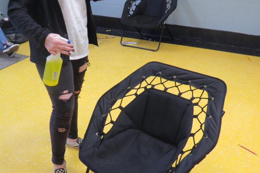 8th grade student disinfects a chair before taking a seat six-feet away from her classmates. Cleaning and disinfecting work areas has became a daily routine among classrooms.