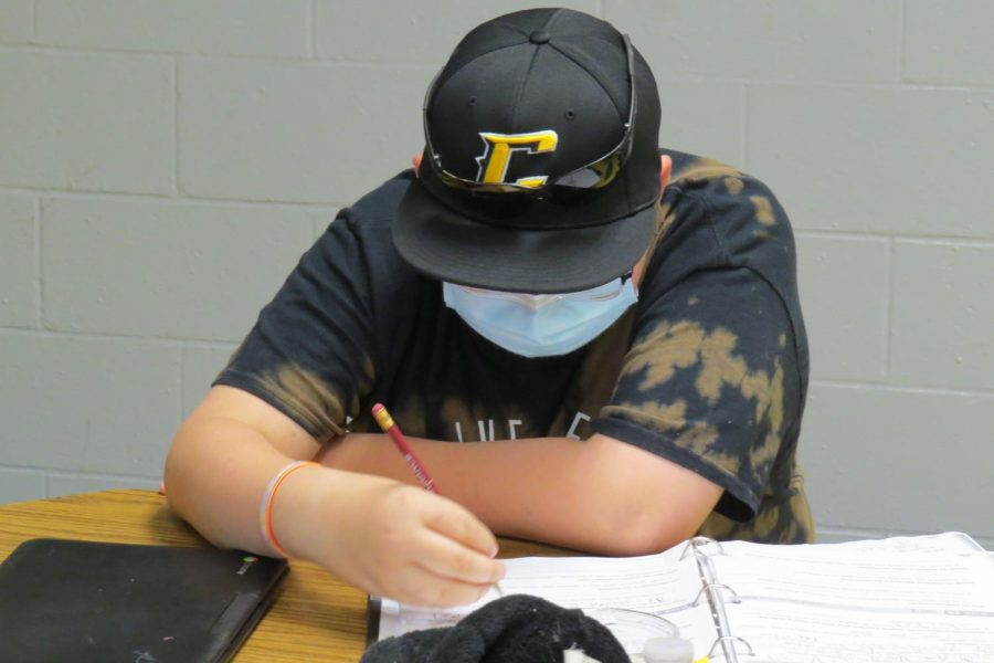 6th grade student wears his mask while working in his daily grammar binder.  Masks are a daily requirement for students when not seating six-feet away from other pupils.